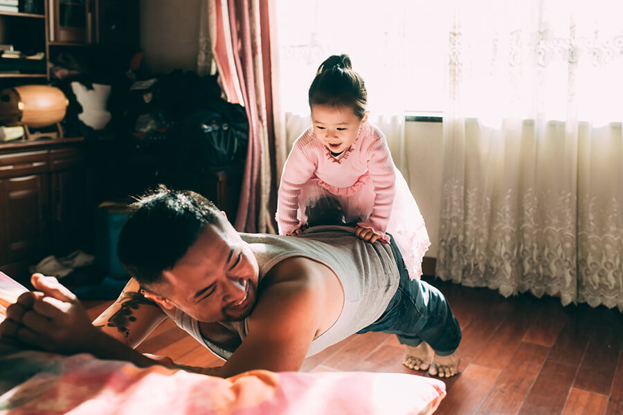 father balancing child on his back